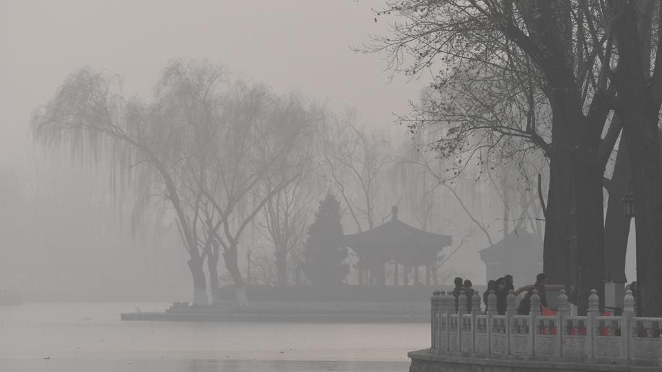 Visitors walk beside a lake on a heavily polluted day in Beijing.