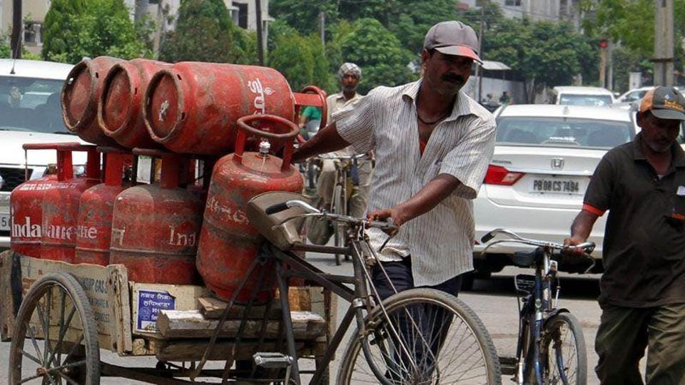 A delivery man carrying LPG cylinders at Kitchlu Nagar in Ludhiana.