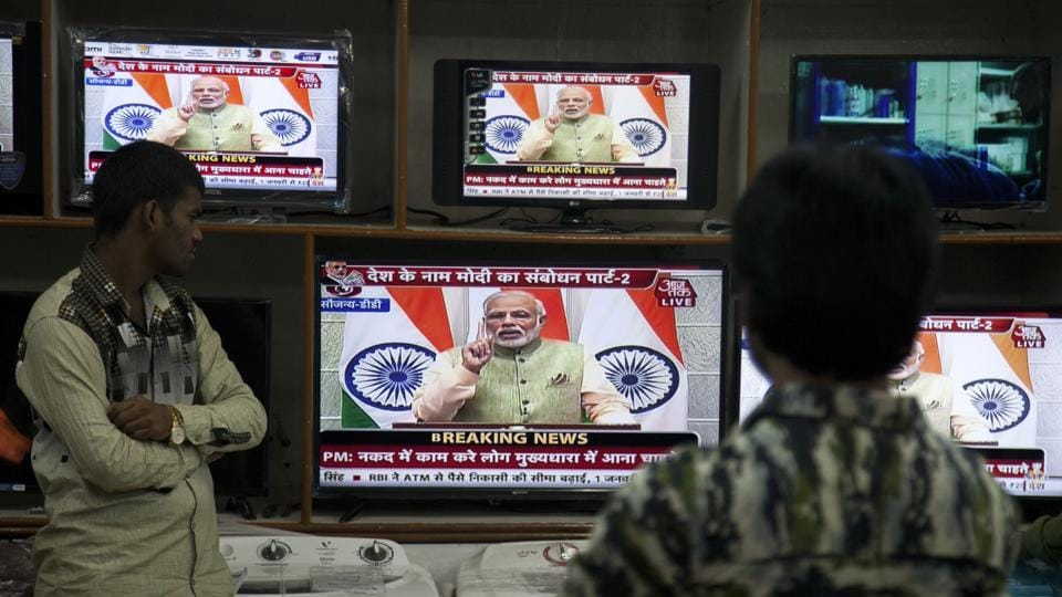 People watch Indian Prime Minister Narendra Modi addressing the nation, on television in Hyderabad, India, Saturday, Dec. 31, 2016. A day after the deadline for depositing old 500- and 1,000-rupee notes, Modi called the demonetisation a purification drive during his Saturday speech.