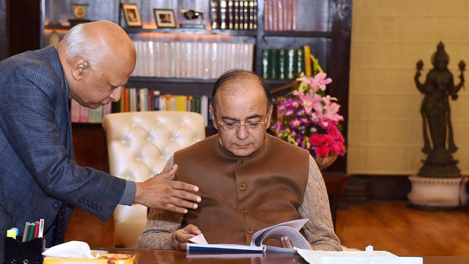 Union finance minister Arun Jaitley goes through a report presented to him, in New Delhi on Friday.
