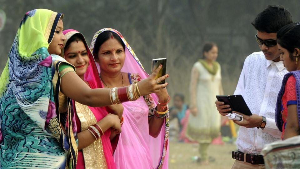 Women take a selfie at Maidan in Kolkata on Sunday. (Ashok Nath Dey/HT PHOTO)