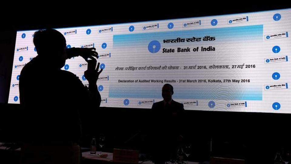 A man takes photo of his colleague with a mobile phone in front of a screen displaying the State Bank of India (SBI) logo before the start of a news conference in Kolkata.