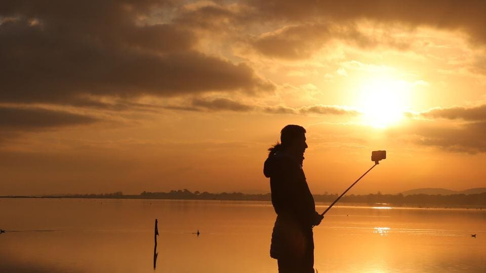 A person holds a selfie stick as the sun sets over a body of water in the Camargue on New Years Eve
