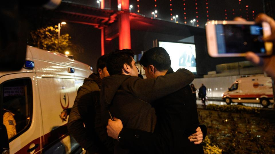 Youths embrace near the scene of an attack in Istanbul, on New Year's Day, early Sunday, Jan. 1, 2017. An assailant believed to have been dressed in a Santa Claus costume and armed with a long-barrelled weapon, opened fire at a nightclub in Istanbul's Ortakoy district during New Year's celebrations, killing dozens of people and wounding dozens of others in what the province's governor described as a terror attack. (Depo Photos via AP)