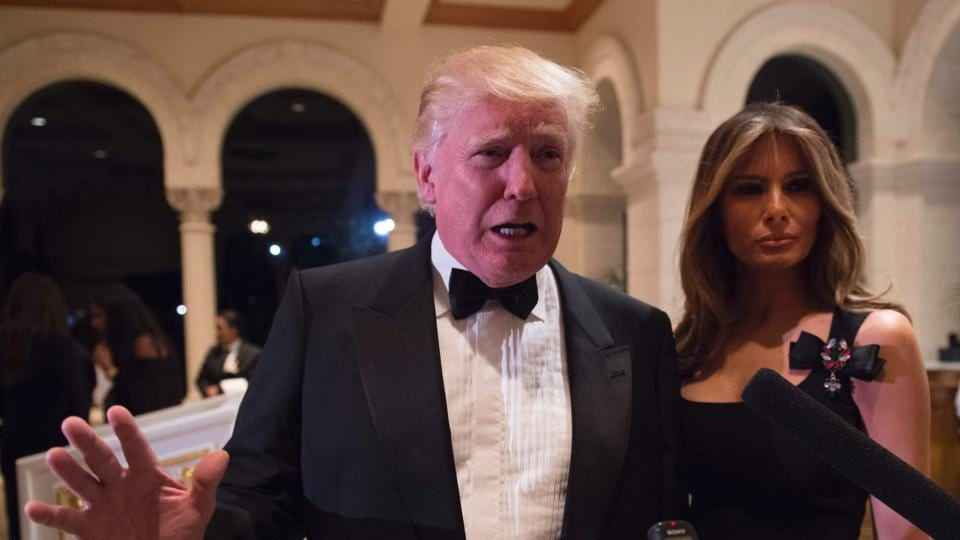 US President-elect Donald Trump answers questions from reporters accompanied by wife Melania for a New Year's Eve party at Mar-a-Lago in Palm Beach, Florida. /