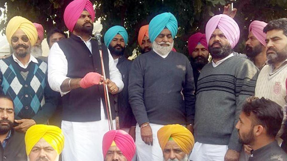 Congress candidate from Khemkaran Sukhpal Singh Bhullar addressing a gathering as his father Gurchet Singh Bhullar (center) and brother Anoop Bhullar (second from right) look on during road show at Khemkaran on Sunday.