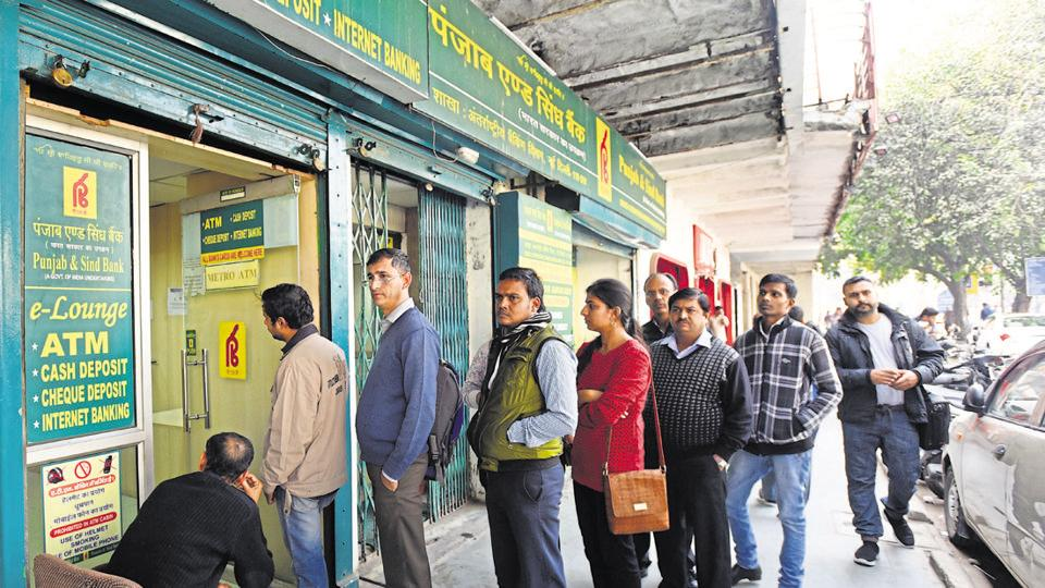 People queue up outside Punjab and Sind Bank Bank ATM to withdraw cash near Connaught Place in New Delhi.