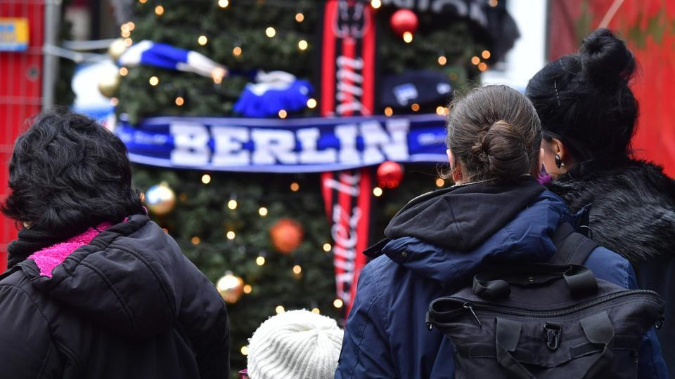 People mourn at a makeshift memorial for the victims of the Christmas market attack near the Kaiser-Wilhelm-Gedaechtniskirche (Kaiser Wilhelm Memorial Church) in Berlin.