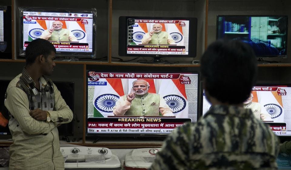 People watch Prime Minister Narendra Modi's address to the nation on December 31.