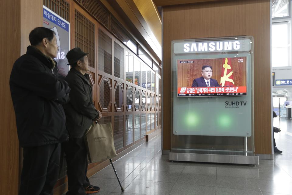 South Koreans watch a TV news program showing North Korean leader Kim Jong Un's New Year speech, at the Seoul Railway Station in Seoul. North Korea's development of banned long-range missiles is in