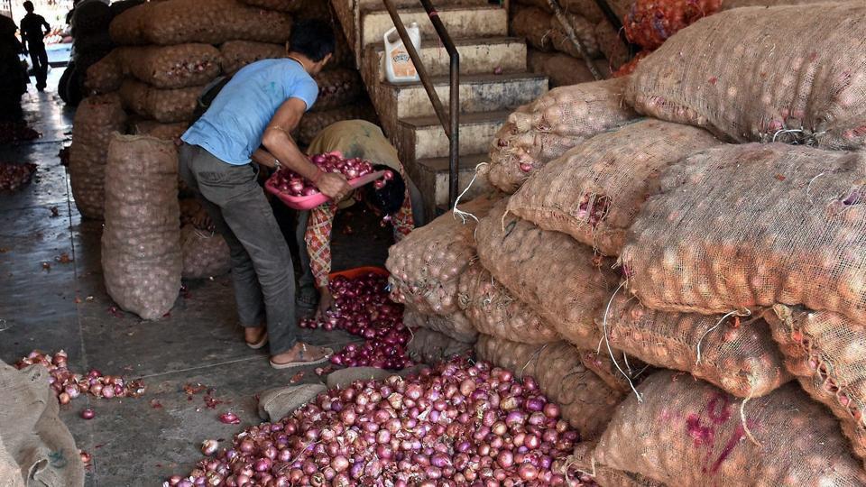 Labourers unload onion sacks.