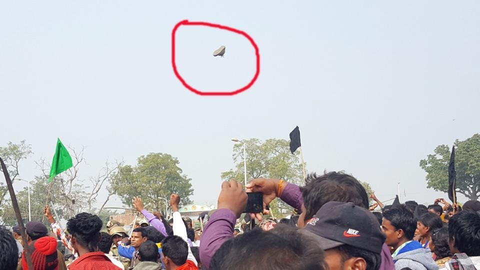 Locals wave black flags and hurl shoes (one encircled in red) at chief minister Raghubar Das inside Shahid Park in Kharsawan on Sunday.