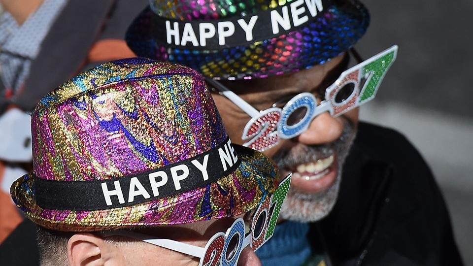 Two parade-goers wearing New Year's hats and glasses await the start of the 128th Rose Parade. (AFP Photo)