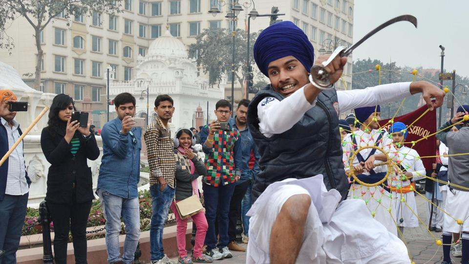 A student of one of the schools  under the Chief Khalsa Diwan performs gatka, a traditional Sikh martial art, in a nagar kirtan during the 350th birth anniversary celebrations of Guru Gobind Singh, in Amritsar on Tuesday. (Sameer Sehgal/HT)