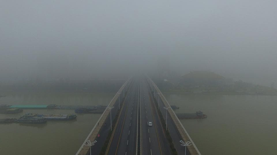 Cars cross a bridge through a thick layer of fog in Yangzhou, in China's eastern Jiangsu province. Thick fog reduced visibility in the city, sometimes down to 50 metres.  (AFP)