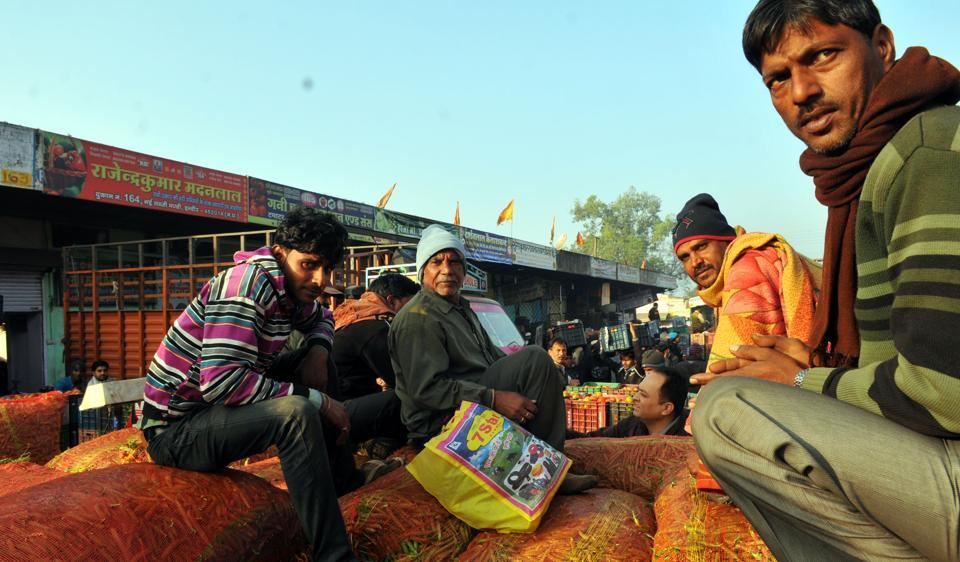 Farmers wait for their turn to sell sacks of green peas at Choithram mandi in Indore on Monday.