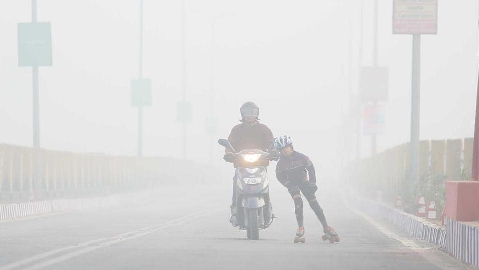 A Child practices roller skates with a guardian on deserted Jaipur Ajmer Highway even as fog coves the city, in Jaipur, Rajasthan. (Himanshu Vyas/HT Photo)