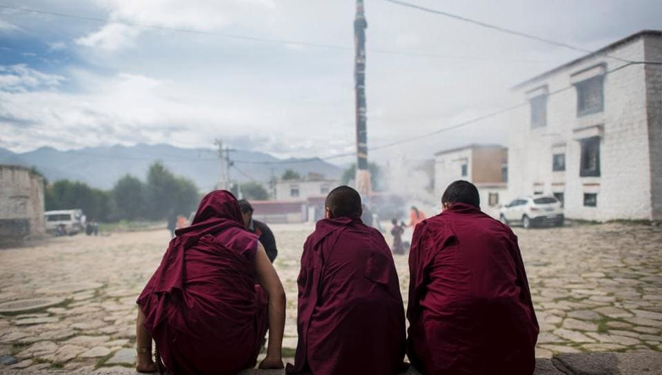 Monks sit in front of the Buddhist Sera monastery in the regional capital Lhasa, Tibet.
