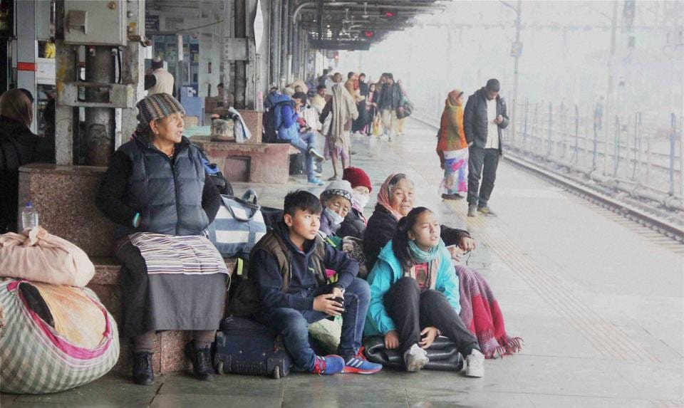 Stranded passengers wrap themselves in warm clothes as they wait for their trains, delayed due to fog in Allahabad. (PTI)