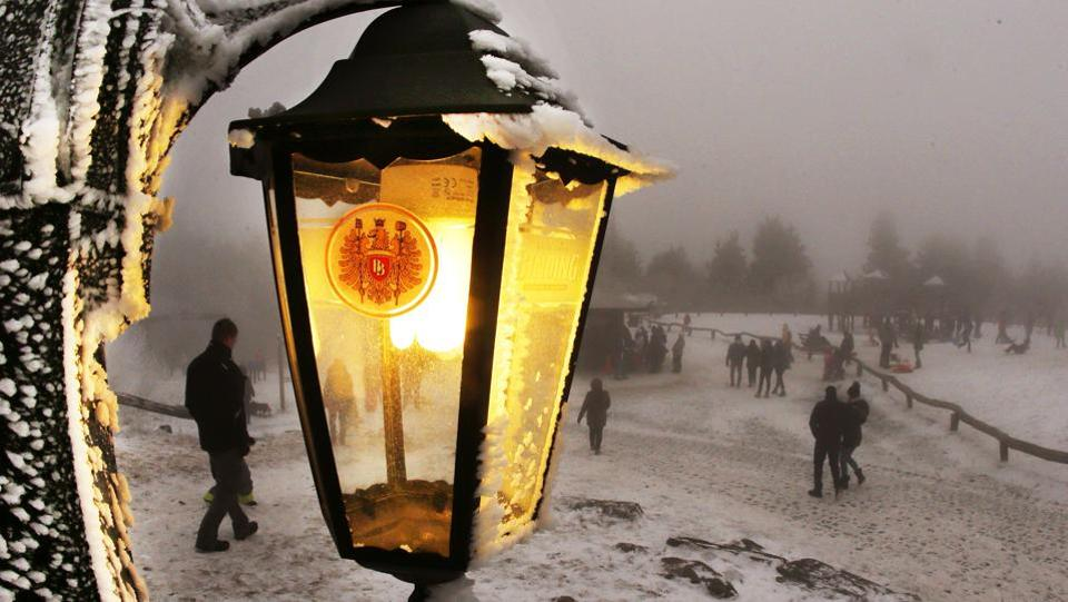 A lamp of a restaurant shines as trippers walk by in thick fog on top of the 880 m high Feldberg mountain near Frankfurt, Germany. (Michael Probst/AP)