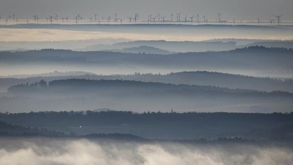 Wind turbines seen on the horizon as the peaks of Taunus foothills rise out of the fog-covered valleys at Grosser Feldberg near Frankfurt, central Germany.  (Frank Rumpenhorst/AP)