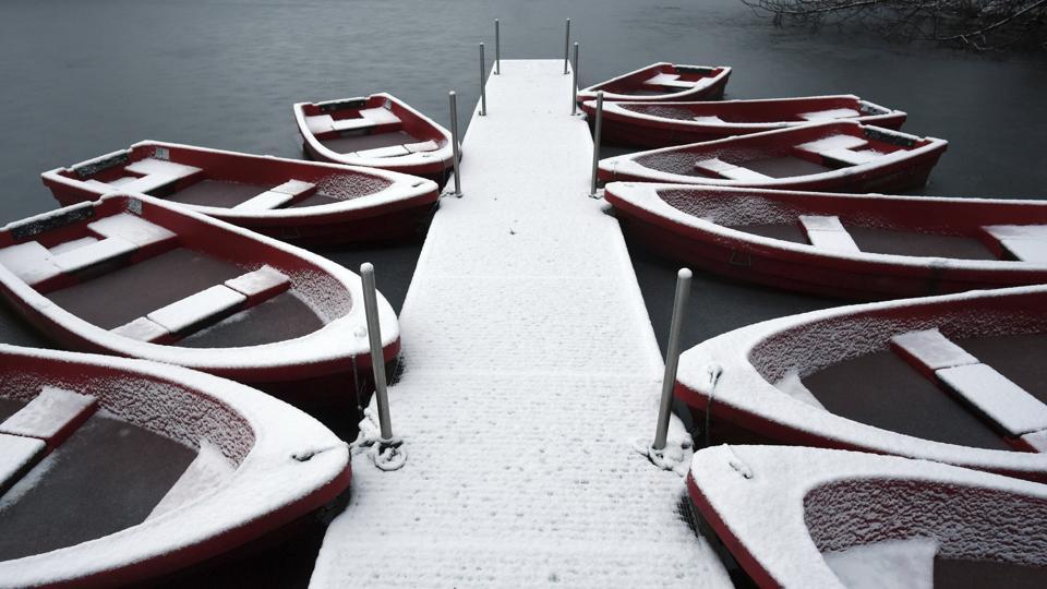 A film of white snow covers rowing boats docked at the Decksteiner Weiher ponds in Cologne, western Germany. (AP)