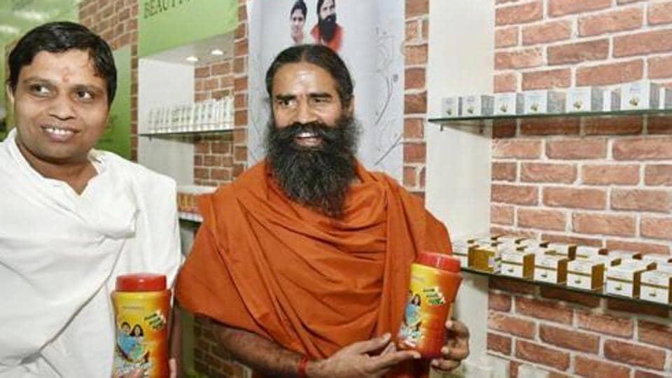 Baba Ramdev and Acharya Balkrishna display Patanjali products.