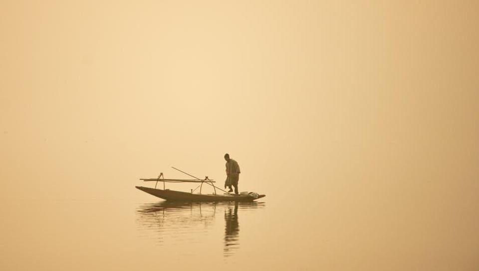 A fisherman sails his boat through dense fog day on the Dal Lake in Srinagar. (ATauseef Mustafa/FP)