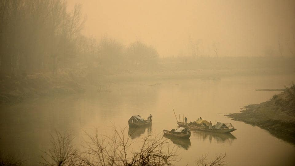 Kashmiri boatmen extract sand from river Jhelum on a foggy morning on the outskirts of Srinagar . A cold wave further tightened its grip in Jammu and Kashmir with most places in the state recording sub-zero temperatures.  (AFP)
