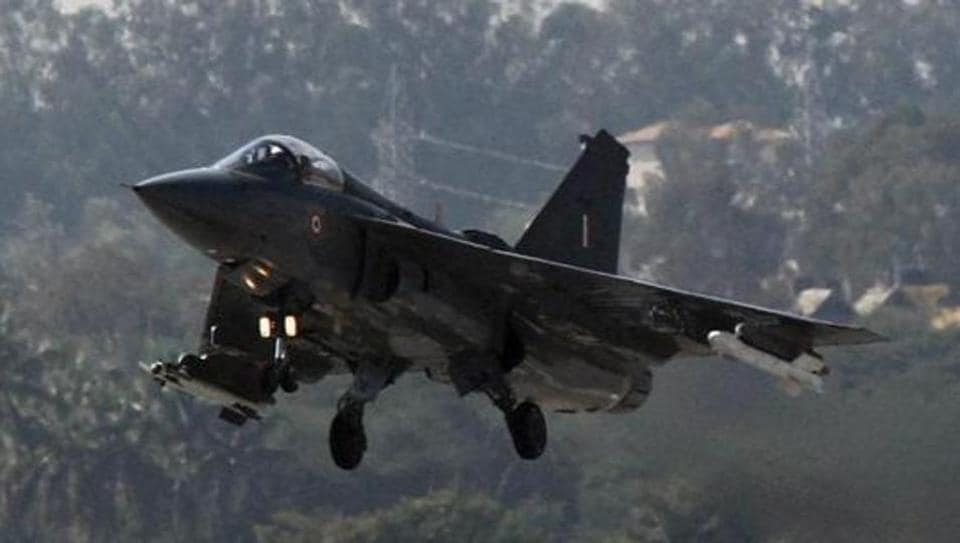 A Tejas aircraft flies during the initial operational clearance before its induction into IAF at Hindustan Aeronautical Ltd airport in Bengaluru.
