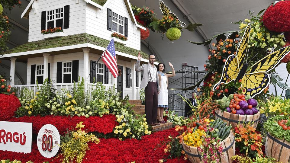 An actor and actress depicting RAGU founders, Assunta and Giovanni Cantisano, ride on the float 'Simmered in Tradition' during judging for the 128th Rose Parade on Sunday, Jan. 1, 2017 in Pasadena, California. (AP Phoyo)