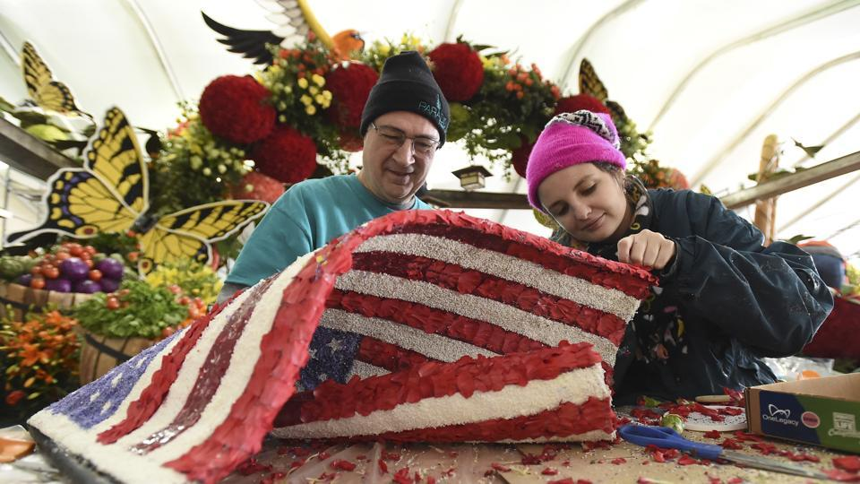Volunteers finish up an American Flag covered entirely in organic material for the RAGU 80th anniversary float. (AP Photo)
