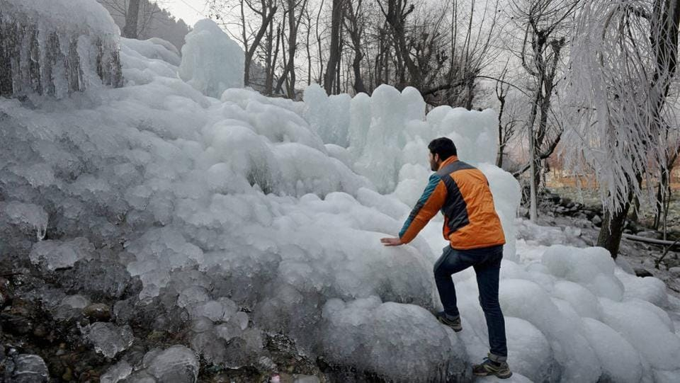 A man tries to climb huge icicles at Kokarnag in Kashmir's Anantnag area.   (PTI)