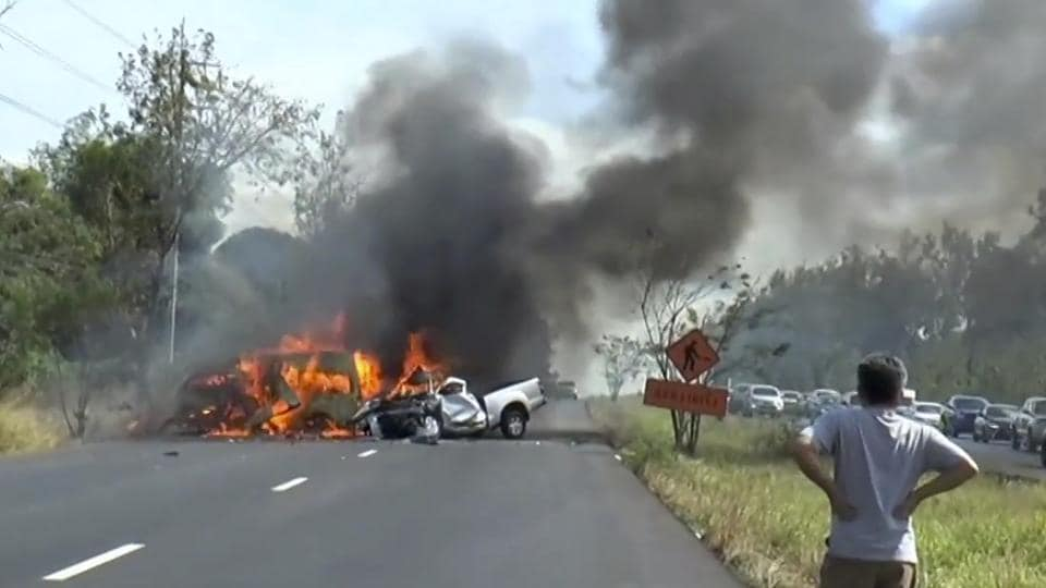 In this image made from video, a man watches as two vehicles burn after they collided on a highway east of Bangkok, Thailand.