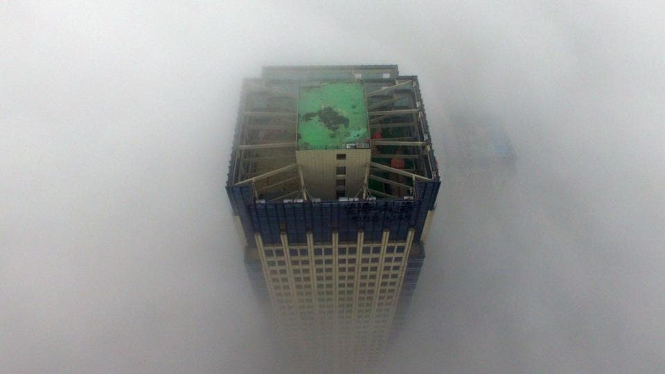 A building appears through a thick layer of fog in Yangzhou, in China's eastern Jiangsu province. Thick fog reduced visibility in the city, sometimes down to 50 metres.  (AFP)