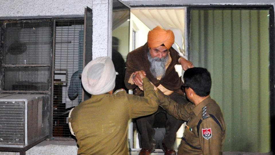 Dean, academic affairs, Gurnam Singh coming out of a window of the administrative block with police help at Punjabi University in Patiala on Wednesday.