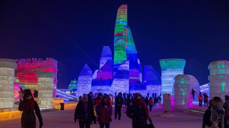 People visit ice sculptures illuminated by coloured lights at the Harbin Ice and Snow Festival to celebrate the new year in Harbin on January 4, 2017.  (NICOLAS ASFOURI / AFP)