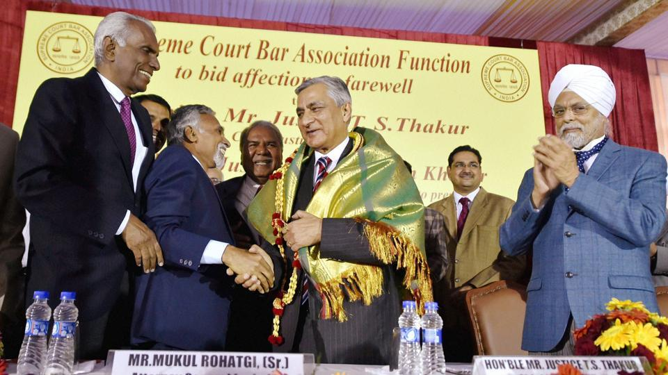 Outgoing Chief Justice of India Justice TS Thakur is greeted with a shawl as CJI-designate Justice JS Khehar looks on, during his farewell ceremony in New Delhi on Tuesday.
