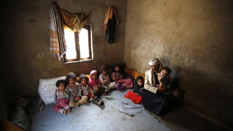 In this Monday, March 28, 2016 photo, Faisal Ahmed, whose infant son, Udai Faisal, died of severe acute malnutrition, sits with his nine remaining children at his house in Hazyaz village on the southern outskirts of Sanaa, Yemen.