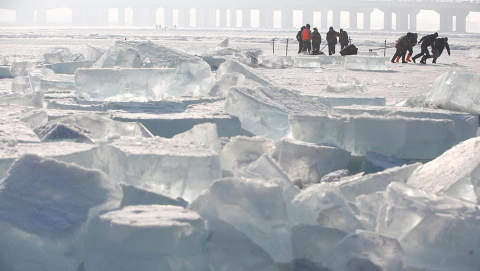 Workers pull a giant ice cube out of the frozen Songhua River as they extract ice to make sculptures for the upcoming Harbin International Ice and Snow Sculpture Festival, in Harbin, Heilongjiang province, China, December 17, 2016.  (Aly Song / REUTERS)
