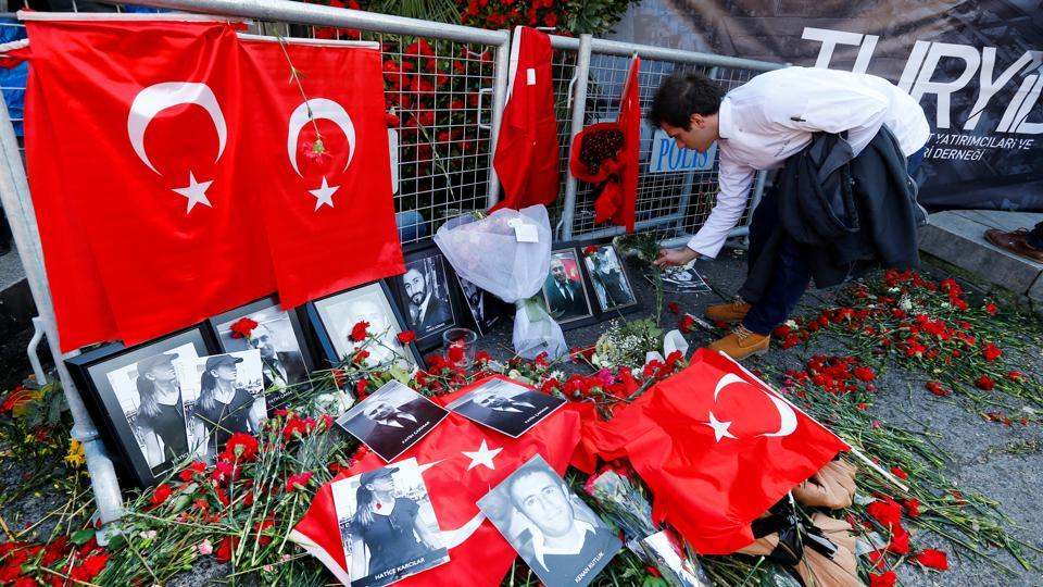A man places flowers at the entrance of Reina nightclub, which was attacked by a gunman, in Istanbul, Turkey.
