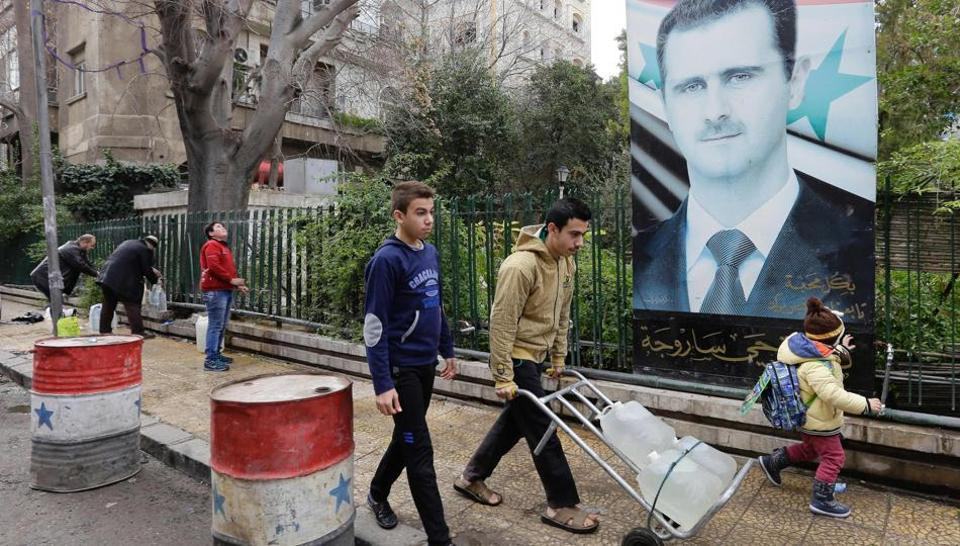 Syrians fill plastic containers with water at a public fountain in the capital Damascus on January 3, 2017. The regime of President Bashar al-Assad is trying to seize control of the region which supplies the main drinking water for four million inhabitants of the capital and surrounding areas.