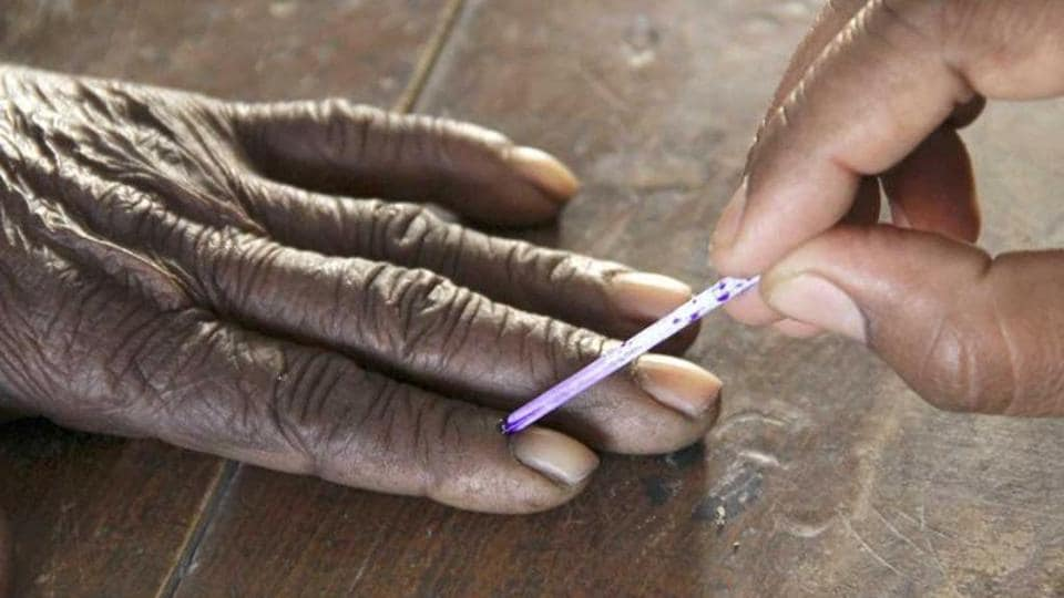 A voting official marks the finger of a voter inside a polling booth during the second phase of state elections, in Azamgarh, Uttar Pradesh.
