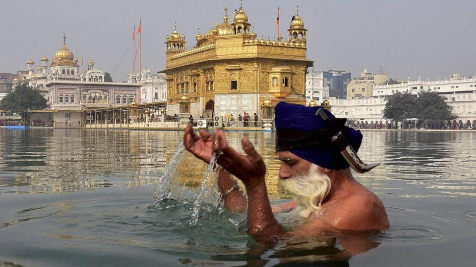 A Sikh devotee takes dip in the holy sarovar on the occasion in the Golden Temple premises in Amritsar on Thursday. (PTI)