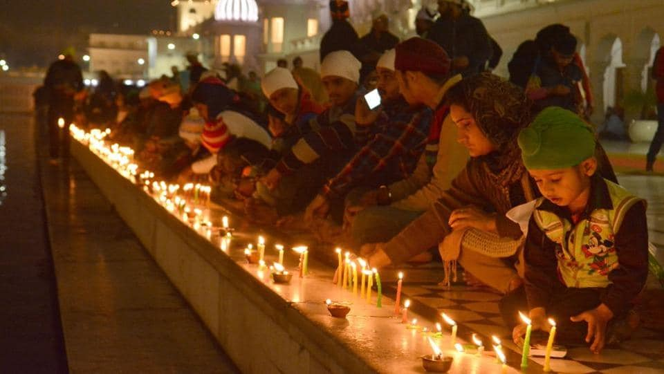 Devotees light candles at Golden Temple on the occasion of 350th birth anniversary of Guru Gobind Singh on Thursday.  (Sameer Sehgal/HT Photo)