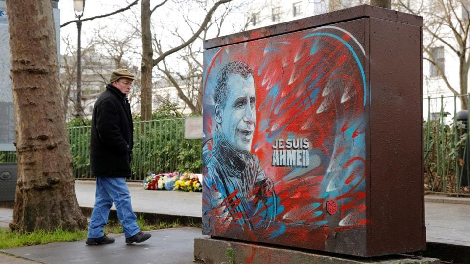 A man walks past a tribute to a slain police officer not far from the old offices of the satirical Charlie Hebdo magazine where two brothers armed with assault rifles shot and killed 11 people, including most of the publication's cartoonists and writers, on January 7, 2015, as France pays tribute two years later in Paris on Thursday.