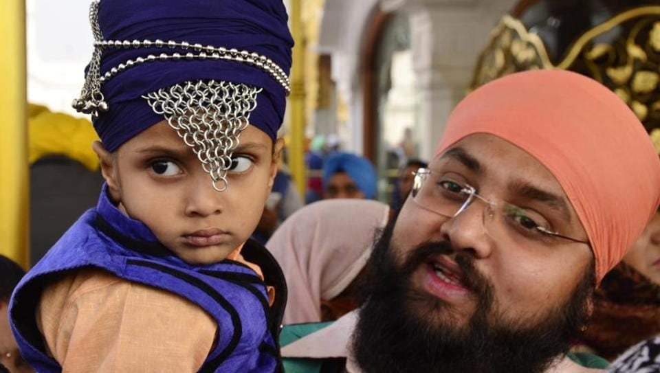A Sikh boy with his family paying obeisance at Golden Temple on Thursday.  (Sameer Sehgal/HT Photo)