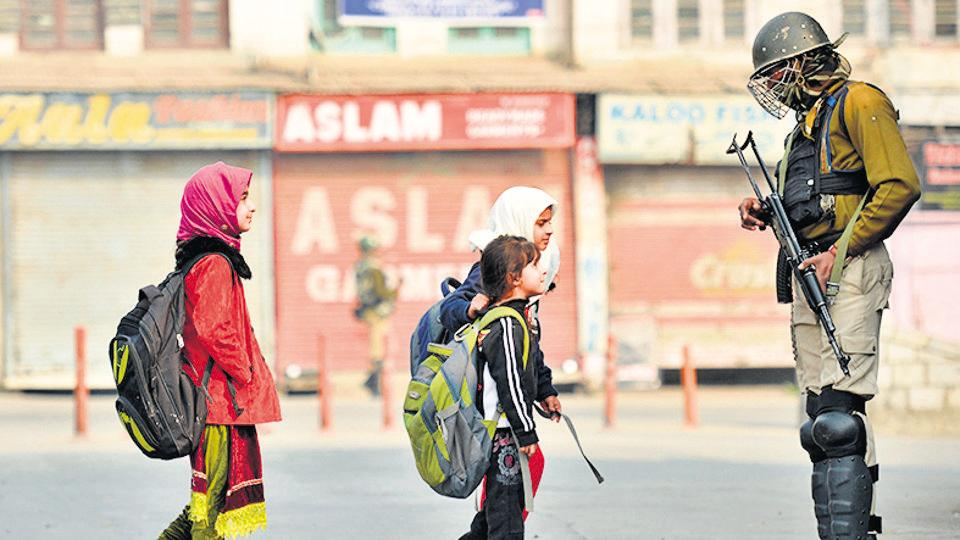 Kashmiri residents walk past a paramilitary trooper standing guard during curfew and restrictions in downtown Srinagar during Kashmir unrest.