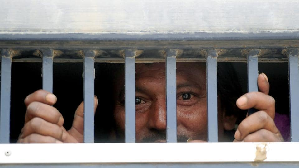 An Indian fisherman stands in a prison van on his arrival at the railway station in Karachi, after his release from prison.