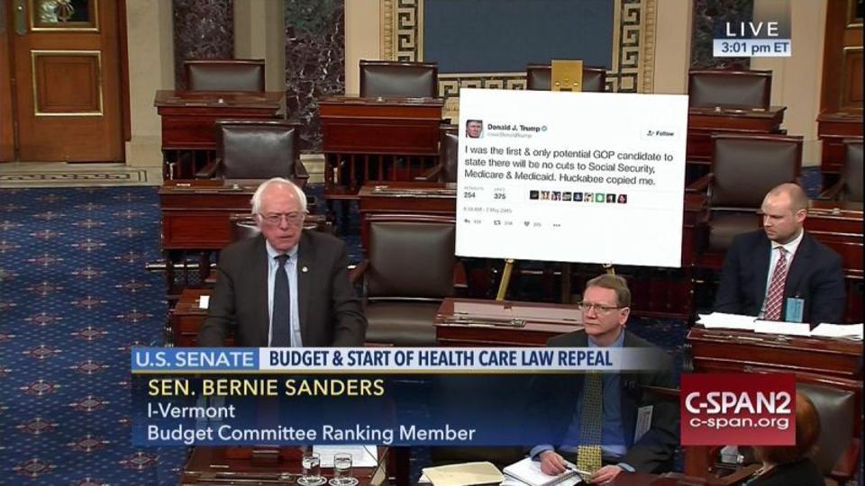 TV screengrab of Bernie Sanders speaking at the USSenate. Behind him a printout of tweet by Donald Trump